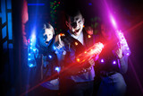 Young people with laser pistols in bright beams - 222825298