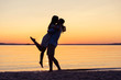 Leinwanddruck Bild - Silhouette of happy couple on beach at sunset, man taking the girl in his arms.