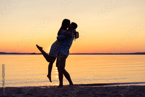 Silhouette of happy couple on beach at sunset, man taking the girl in his arms. - 222831272