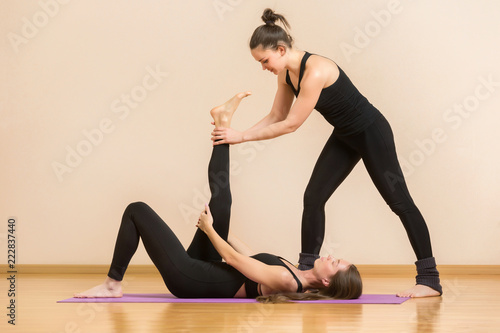 Poster Fitness trainer is helping young woman make exercise stretching her leg at gym background.