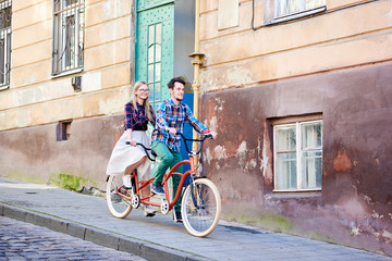 Young couple, handsome bearded man and pretty blond woman in glasses riding together tandem double red bicycle along paved sidewalk on bright sunny summer day by old buildings