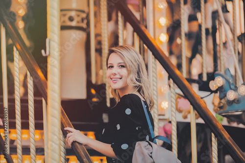 Leinwanddruck Bild Young style girl in sunglasses and black dress stay in merry go round carousel in Strasbourg, France