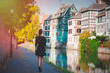 Young style girl in black dress waking along the canal in Strasbourg, France. Autumn season time