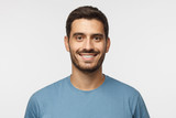 Close up portrait of young smiling handsome guy in blue t-shirt isolated on gray background - 222851624