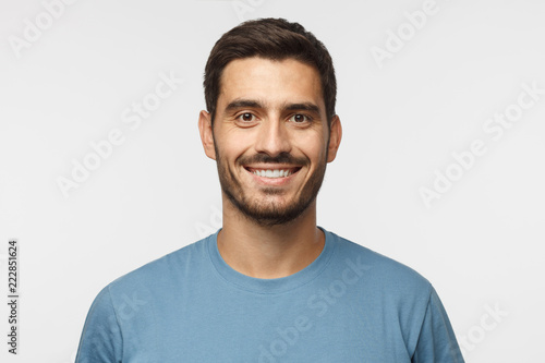 Leinwandbild Motiv Close up portrait of young smiling handsome guy in blue t-shirt isolated on gray background