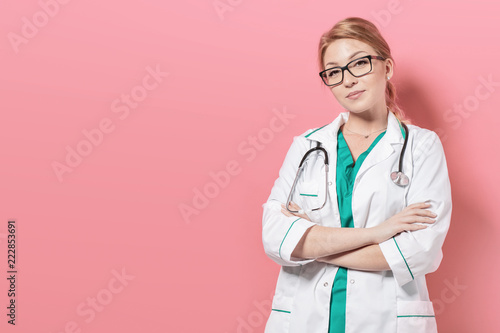 Woman in doctor uniform stands over pink background. Photo with copyspace for your space - 222853691