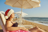 Girl in santa hat on the beach by the sea on Christmas Day. The concept of celebrating Christmas in a seaside resort.