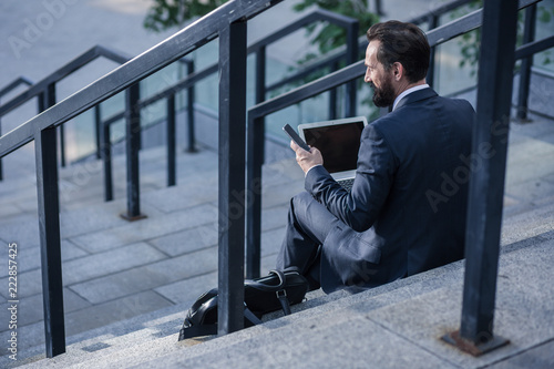 Foto Murales Pleasant bearded businessman sitting on the staircases