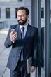 Pleasant professional businessman using his modern phone