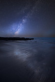 Vibrant Milky Way composite image over landscape of empty beach Summer landscape