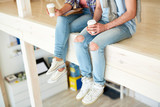 Two young specialists in blue jeans and cross-shoes holding plastic glasses with coffee - 222858691