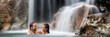 Vacation couple relaxing in waterfall banner. Romantic destination travel holidays people happy together swimming under natural water falls.