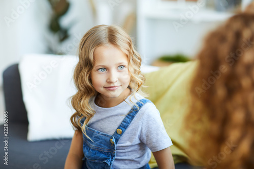 Blonde little girl in casualwear sitting on sofa at home and looking at her mom during talk
