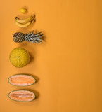 tropical exotic fruits on a yellow background, creative summer concept
