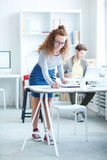 Young casual woman leaning over desk and writing down new creative ideas for project - 222869036