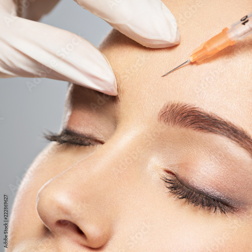 Leinwandbild Motiv Woman getting cosmetic injection of botox near eyes