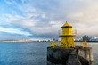 Leinwanddruck Bild - reykjavik lighthouse tower on stone pier in iceland. lighthouse in sea. architecture in seascape and skyline. navigational aid and destination places. wanderlust and travelling to reykjavik, iceland.