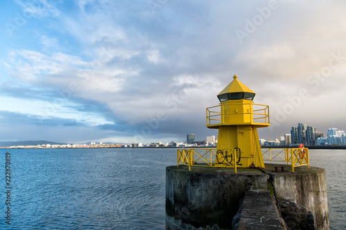 Leinwanddruck Bild reykjavik lighthouse tower on stone pier in iceland. lighthouse in sea. architecture in seascape and skyline. navigational aid and destination places. wanderlust and travelling to reykjavik, iceland.