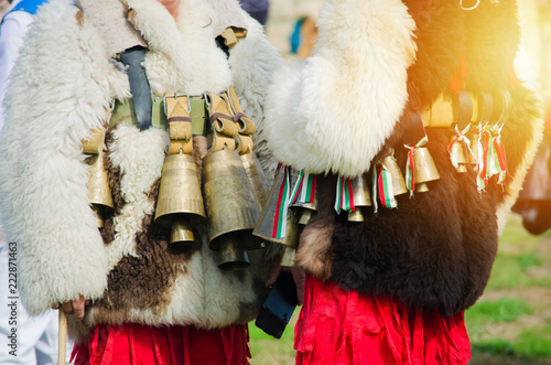 Costumed Bulgarian men Kuker who perform traditional rituals. White furry jackets with bells and ribbons with colors of Bulgaria. Warm sunlight effect. Ethnic celebration © tramster