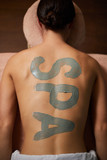 Overview of young relaxed woman back with word spa written with grey clay