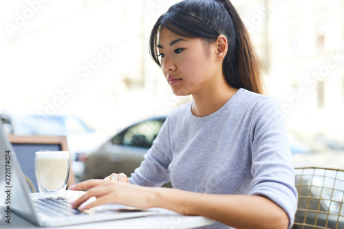 Young Asian student in grey pullover sitting by table in front of laptop, having drink and networking in cafe