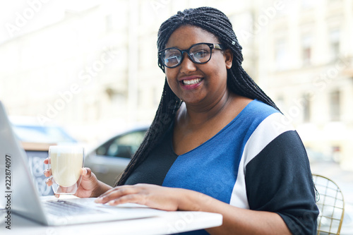 Young mixed-race female student with African braids networking in cafe while having milkshake