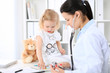 Leinwanddruck Bild - Doctor and patient baby in hospital. Little girl is being examined by pediatrician with stethoscope. Health care, insurance and help concept