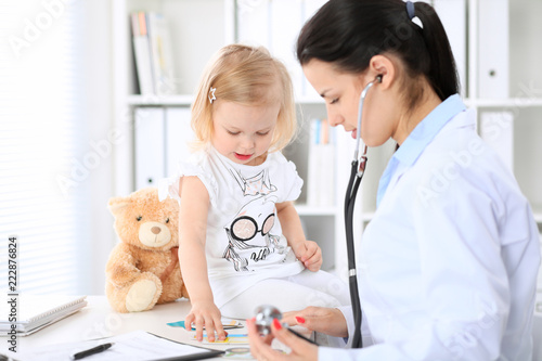 Leinwanddruck Bild Doctor and patient baby in hospital. Little girl is being examined by pediatrician with stethoscope. Health care, insurance and help concept