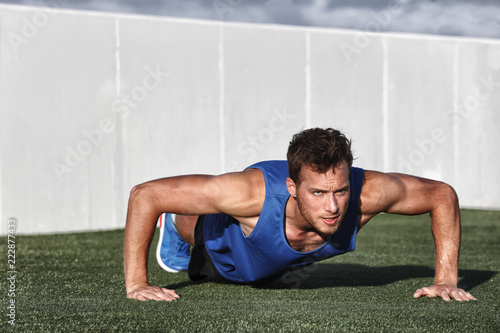 Sportowe fitness męskie push-upy. Męski atlety ćwiczyć pcha up outside w pogodnym świetle słonecznym. Dopasowanie shirtless fitness męski model w CrossFit ćwiczenia na świeżym powietrzu. Pojęcie zdrowego stylu życia.