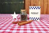 Vintage Behälter für Muskatnuss, Gläschen mit Piment, Zimtstangen auf karierter Tischdecke vor Holzwand - 222882656