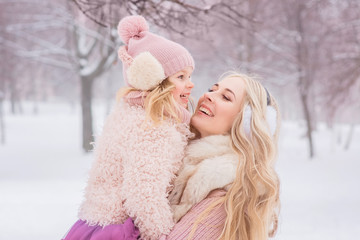 mother with long blond curls hugs her beautiful little daughter in a pink hat with a bubo © beshtanya