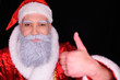 kind and cheerful santa claus on a dark background smiles into the camera and shows thumb of the hand