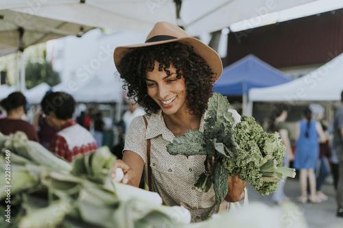 Leinwanddruck Bild Beautiful woman buying kale at a farmers market