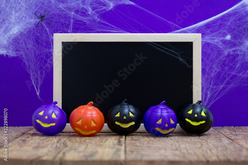 Halloween background concept. Blackboard with decor pumpkins, cobweb on wooden table and purple backdrop - 222898070