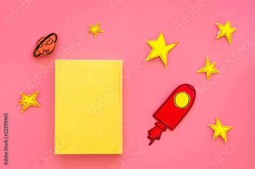 Literature about cosmos for school children. Book with blank cover near cutout of rocket, stars, moon on pink background top view mockup
