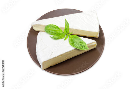 Fototapeta Brie cheese on brown dish on a white background