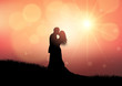 Silhouette of a wedding couple on sunset background