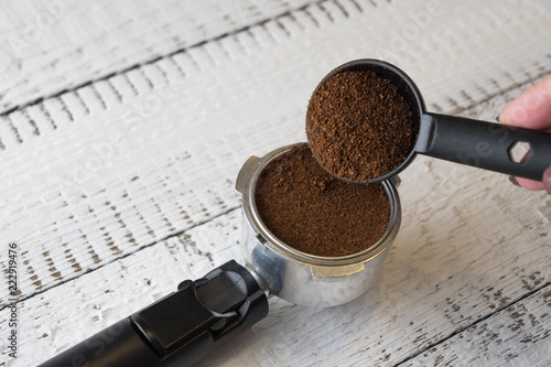 Woman pouring grinded coffee inside a group head of a coffee machine to make a morning espresso. Breakfast and home equipment concept.