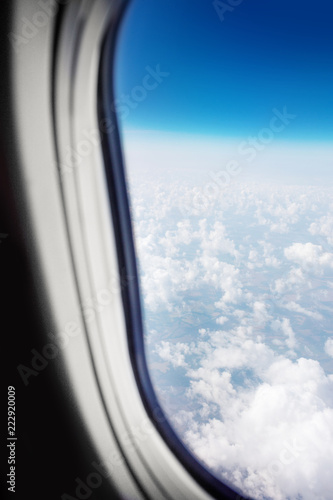 Beautiful Sky above the clouds. View from  the window of an aircraft  with blue sky and fluffy clouds - 222920009