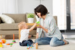 Leinwanddruck Bild - family, child and motherhood concept - happy mother with little baby son playing developmental toys and sippy cup at home