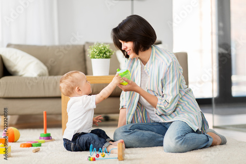 Leinwanddruck Bild family, child and motherhood concept - happy mother with little baby son playing developmental toys and sippy cup at home