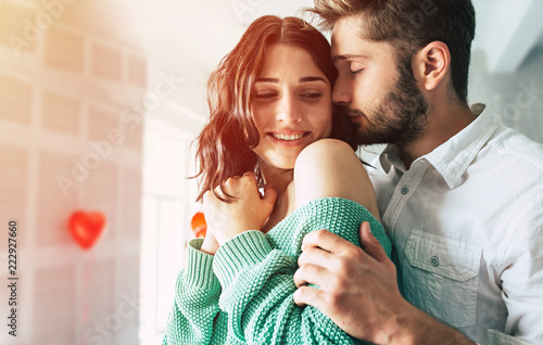 Leinwandbild Motiv Close up photo of Handsome young man is kissing his beloved cute woman in date romantic day