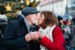 Leinwanddruck Bild - Senior couple on an outdoor Christmas market.