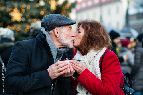 Senior couple on an outdoor Christmas market. - 222931243