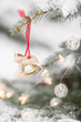 Christmas decoration on a red ribbon on a snowy Evergreen tree outdoors. Winter, Christmas celebration, holidays season.