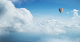 Colorful hot air balloon flying against blue cloudy sky. - 222938897