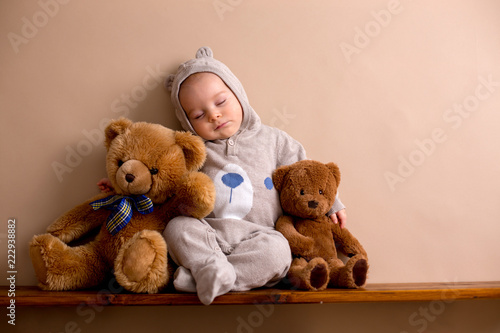 Leinwandbild Motiv Sweet baby boy in bear overall, sleeping on a shelf with teddy bears