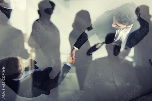 Leinwanddruck Bild Handshaking business person in office. concept of teamwork and partnership. double exposure
