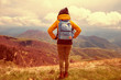 Girl with rucksack on the top of the hilly landscape.