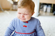 Leinwanddruck Bild - Cute little sad baby girl crying. Hungry or tired child sitting indoors and having tears